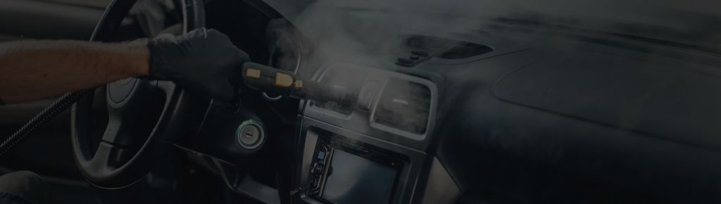 Image depicts a man cleaning the interior of a car.